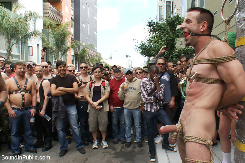 BestBDSM24.com - Image 14051 - Muscle slave is stripped naked, used and humiliated while hordes of people take photos.